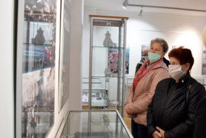 Uczestnicy wystawy oglądają zdjęcia ipamiątki