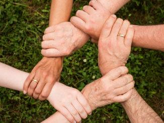 Symbol wsparcia - ręce 5 osób, które trzymają się razem