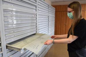 Pracownik urzędu wyciąga stare mapy zszuflady