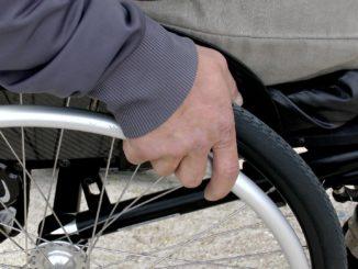 Ręka na kole wózka dla osób niepełnosprawnch