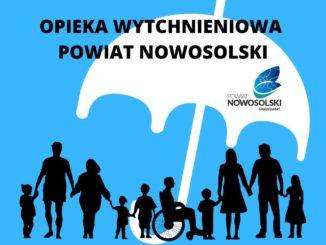 Grupa ludzi w różnym wieku, w tym osoba niepełnosprawna na wózku pod parasolem z logiem powiatu