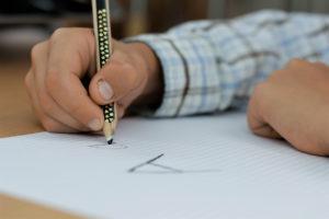 Dziecko pisze literki nakartce